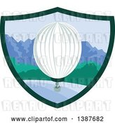 Vector Clip Art of Retro Hot Air Balloon over Mountains and the Ocean in a Shield by Patrimonio