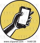 Vector Clip Art of Retro Woodcut Hand Holding a Smart Phone in a Yellow and Black Circle by Patrimonio